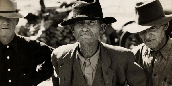 Dorothea Lange photo of three men, ex-temant farmers, wearing hats and covered in dust