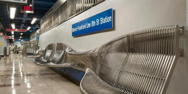 A wavy bench on the train platform offers seating but no place to lie down