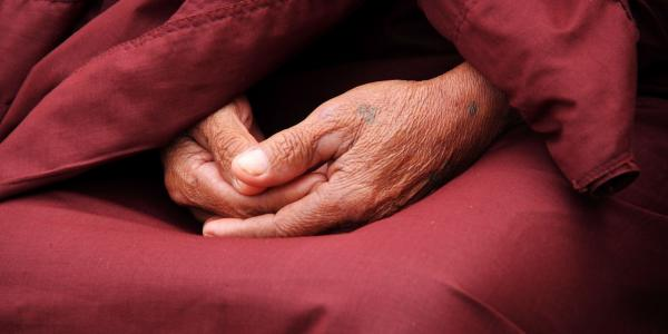 hands folded in a lap with burgundy monk's robes